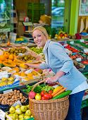 a young woman buying fruits and vegetables at a weekly market. healthy diet.