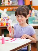 Cute little preschool girl painting at desk in art class
