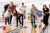 stock photo of indoor games  - Young friends bowling while people cheering in club - JPG