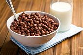 chocolate cereals in bowl and milk on wooden table