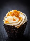 Delicious caramel cupcake on black background