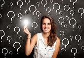 young woman holding a lightbulb in front of chalkboard with interrogation symbols
