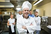 Head chef posing with team behind him in a professional kitchen