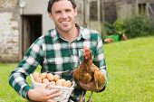 Happy young man holding his chicken and basket of eggs in his garden