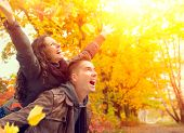 Happy Couple in Autumn Park. Fall. Young Family Having Fun Outdoors. Yellow Trees and Leaves. Laughi