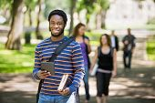 Portrait of happy male student holding digital tablet on campus with friends in background