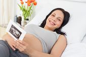 Portrait of smiling pregnant woman holding sonography report while lying in bed at hospital