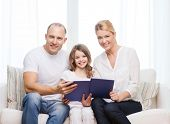 family, child and home concept - smiling parents and little girl with book at home