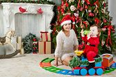 Mother in santa cap sits on floor under decorated Christmas tree near little girl dressed in Santa suit which sits on toy plastic steam engine and drink from bottle