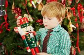 stock photo of nutcracker  - Little boy looks at Nutcracker he holds in his hands - JPG