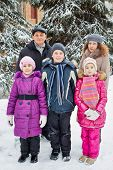 Family of five stands outside in winter under snow-covered firtrees