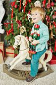 stock photo of nutcrackers  - Smiling little boy rides on rocking horse near christmas tree - JPG