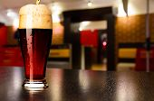 glass of fresh draft dark beer on table in pub