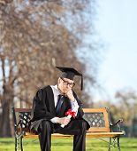 Sad graduate student sitting on a bench in park shot with tilt and shift lens