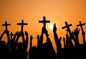 Silhouette of Crosses Held Up at Sunset