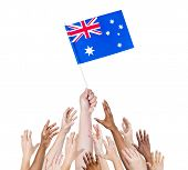 Diverse Multiethnic Hands Holding and Reaching For The Flag of Australia