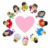 stock photo of pre-adolescents  - Smiling Diverse Children Around a Heart - JPG