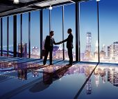 stock photo of handshake  - Businessmen Shaking Hands With City View - JPG