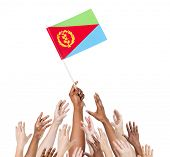 Group Of Multi-Ethnic People Reaching For And Holding The Flag Of Eritrea