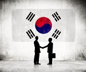 Two Businessmen Shaking Hands With Flag of South Korea