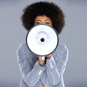 African American woman speaking into a megaphone making a public announcement with her face partiall