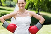 Portrait of young bride wearing boxing gloves with hands on waist in garden