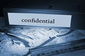 The word confidential on blue business binder on a desk