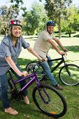 Portrait of happy couple riding bicycles in parkland