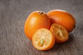 image of kumquat  - fresh kumquat on wood table close up photo - JPG