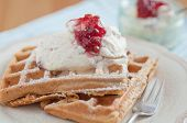 Home made waffles with jam and whipped cream