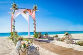 stock photo of gazebo  - wedding arch decorated with flowers on tropical sand beach - JPG