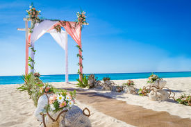 pic of cabana  - wedding arch decorated with flowers on tropical sand beach - JPG