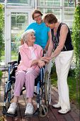 Elderly Patient On Wheel Chair With Two Caregivers