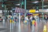Central Hall Of Schiphol Airport With Travellers, Information Panels And Shops
