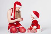 Happy mother with little daughter iin the Santa Claus clothes