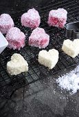 Making Australian Style Pink Heart Shape Small Lamington Cakes On Baking Rack With Strawberry Sauce