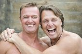 foto of gay couple  - A colour portrait photo of a happy laughing and sexy gay male couple cuddling up to each other outdoors - JPG