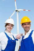 Two Engineers Posing With Wind Turbine And Solar Panels