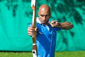 pic of archer  - Bowman or archer aiming at target with bow and arrow - JPG
