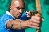 picture of longbow  - Bowman or archer aiming at target with bow and arrow - JPG
