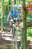 Man Rides Bicycle On Tightrope At High Rope Course