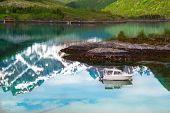 Small fishing boat in scenic fjord on Lofoten, Norway