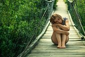 picture of saddening  - Lonely sad girl sitting on the suspension bridge - JPG