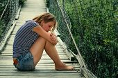 Portrait of a pensive lonely girl on the bridge