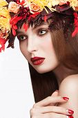 Beautiful red-haired girl with bright autumn wreath of leaves and flowers. Beauty face.