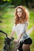 Beautiful girl wearing white lace blouse and black sexy shorts having fun in park with bicycle