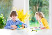 Two Happy Kids drawing, painting and cutting colorful paper butterflies