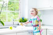 Funny curly toddler girl washing dishes, cleaning with a sponge and playing with foam in the sink