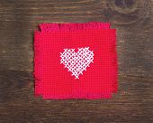 Cross stitched heart on dark wood