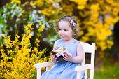 Cute Toddler Girl Enjoying Egg Hunt In The Garden